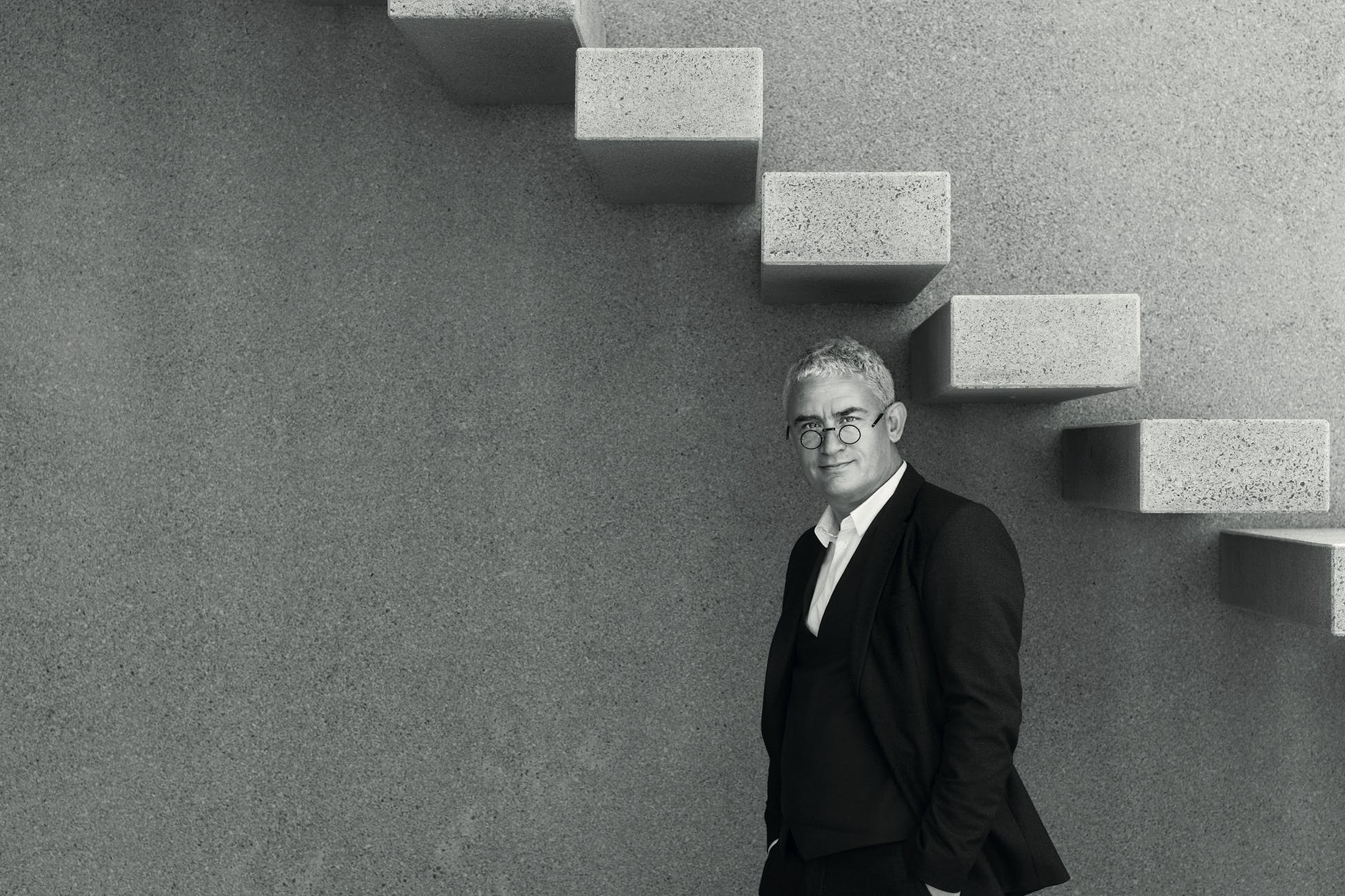 a man standing under a concrete staircase